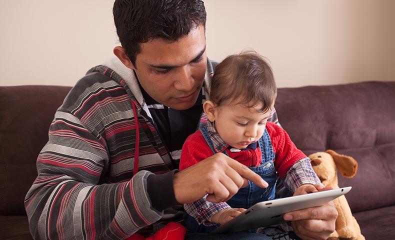 タブレットを子どもに使わせる外国人の父親