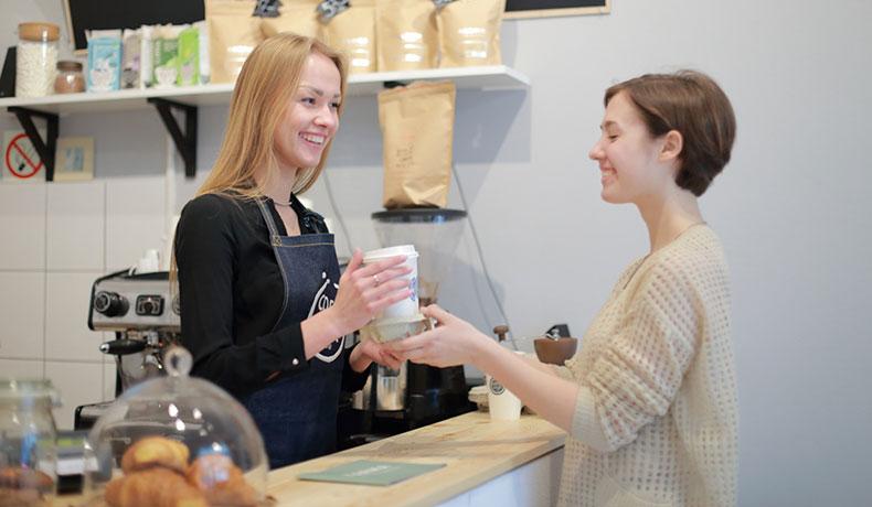 コーヒーを渡す女性店員