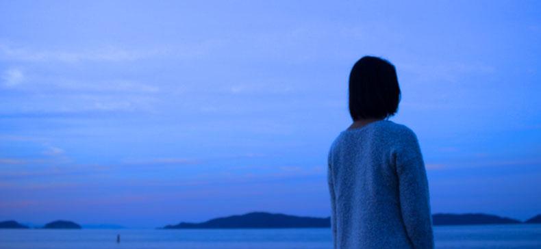 一人で海辺を歩く女性