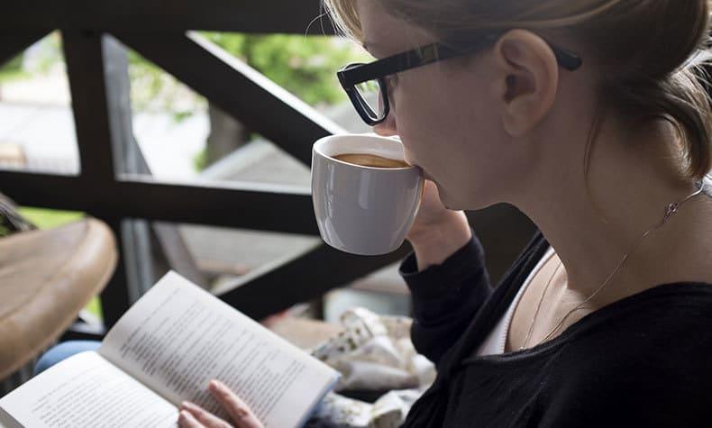 コーヒーを飲みながら読書する女性